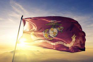 United States Marine Corps flag textile cloth fabric waving on the top sunrise mist fog