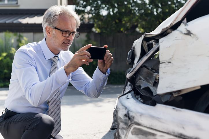 Man taking photos of a hit car